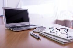 Träkontorsskrivbord med bärbara datorn, pennor, exponeringsglas arkivbilder