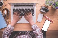 Träkontorstabell med affärsmannen som skriver på anteckningsboktangentbordet, lattekaffekoppen och den tomma skärmen på mobil arkivfoton