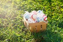 Träkorg med gula och gröna ägglögner för apelsin, på grönt gräs för vår på solljus Lycklig påsk! Garnering äggjakt arkivbild
