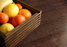 Träkorg med tropiska frukter Saftiga mandariner, apelsin, citron och banan Mogna frukter för sött vitamin Royaltyfria Bilder