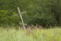 Träkristet kors i blommafältet och skogbakgrunden arkivbilder