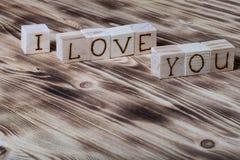 Träkuber med inskriften ÄLSKAR JAG DIG på ny träbakgrund Arkivfoton