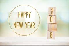 Träkuber med 2018 och lyckligt nytt år över suddighetsbokehbackgr fotografering för bildbyråer