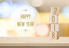 Träkuber med 2018 och lyckligt nytt år över suddighetsbokehbackgr royaltyfri fotografi
