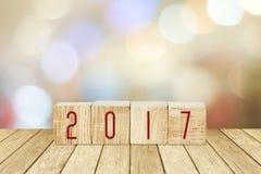 Träkuber med 2017 på perspektivträ över suddighetsbokehbackg Royaltyfri Bild