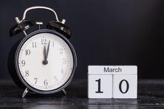 Träkubformkalender för mars 10 med den svarta klockan Arkivfoto