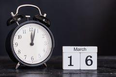 Träkubformkalender för mars 16 med den svarta klockan Arkivfoto