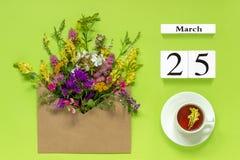 Träkubkalendermars 25 Kopp av örtte, kraft kuvert med mång- kulöra blommor på grön bakgrund Begreppshälsningar royaltyfri bild