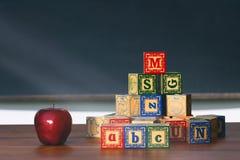 Träkvarter och äpple på skrivbordet Arkivfoton