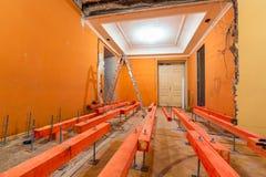 Träkvarter på dubbarna för att lyfta upp förfallen installerande rörmokeri och kanalisering för golv och stege under golv I royaltyfri bild