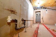 Träkvarter på dubbarna för att lyfta upp förfallen installerande rörmokeri och kanalisering för golv och stege under golv I arkivfoton