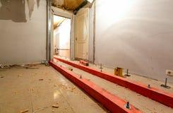 Träkvarter på dubbarna för att lyfta upp förfallen installerande rörmokeri och kanalisering för golv och stege under golv I royaltyfria foton