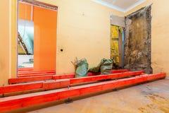 Träkvarter på dubbarna för att lyfta upp förfallen installerande rörmokeri och kanalisering för golv och stege under golv I arkivfoto