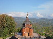 Träkyrka i en bergby, höstnatur, Ryssland Arkivfoto