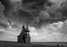 Träkyrka på överkanten av kullen Sikt för Vershinino bysolnedgång Arkhangelsk region, nordliga Ryssland royaltyfri foto