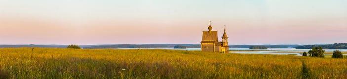 Träkyrka på överkanten av kullen Sikt för Vershinino bysolnedgång Arkhangelsk region, nordliga Ryssland fotografering för bildbyråer
