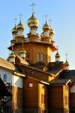 Träkyrkan med guld- kupoler invigdes av solen mot en bakgrund för blå himmel Ryssland Belgorod Royaltyfria Bilder
