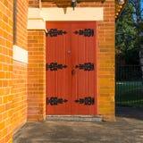 Träkyrklig dörr med järnensemblegångjärn Arkivbilder