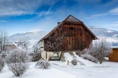 Träladugård som täckas av insnöade österrikiska fjällängar Royaltyfria Foton