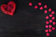 Trälantligt rött dekorativt hjärtahänga och rosor på mörk träbakgrund med utrymme, lägger framlänges Valentin` s arkivbild