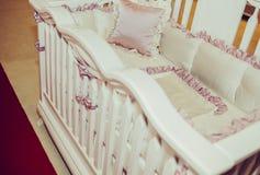 Trälathund och retro siden- sängkläder och kuddar Royaltyfri Foto