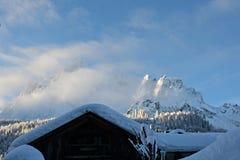 Träloge under en beläggning av vita snö och berg i bakgrunden Arkivfoto