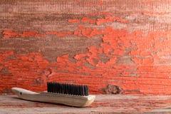 Trälokalvårdborste mot den gamla målade väggen royaltyfria bilder