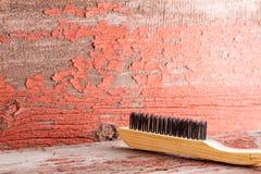 Trälokalvårdborste mot den röda trasiga väggen arkivfoto