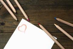 Trämålade blyertspennor och röd hjärta Royaltyfria Foton