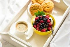 Trämagasin med den smakliga frukosten på säng Espresso, bananmuffin, keso med blåbäret och hallon Arkivfoto