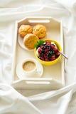 Trämagasin med den smakliga frukosten på säng Espresso, bananmuffin, keso med blåbäret och hallon Royaltyfri Foto