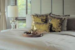 Trämagasinet med guld- blänker kuddar på säng Fotografering för Bildbyråer
