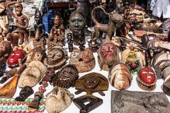 Trämaskeringar och diagram av afrikansk kultur på loppmarknaden I Royaltyfri Bild