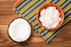 Trämassa av kokosnöten i en bunke och en halva av kokosnöten på en trätabell Fotografering för Bildbyråer
