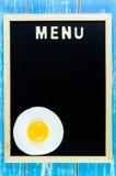 Trämeny för engelskt alfabet och stekt ägg på svart tavla Arkivfoto