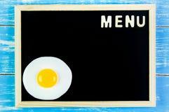 Trämeny för engelskt alfabet och stekt ägg på svart tavla Royaltyfri Fotografi