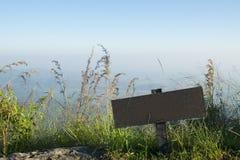 Träminnestavlatecken med gräs- och bergbakgrund arkivbild