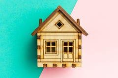 Trämodellhus på geometriska rosa färger och en pastellfärgad bakgrund för turkos med kopieringsutrymme Modell form Handgjort träh Arkivfoton