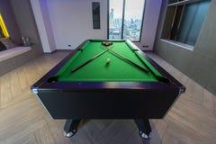 Tränga in i ett hörn den gröna tabellen för pölbiljard med den färdiga uppsättningen av bollar och två pölstickrepliker i ett mod royaltyfri foto