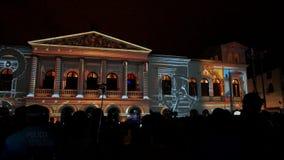 Tränga ihop att beundra anblicken av ljus som projekteras på fasaden av Teatroen Sucre, i den historiska mitten av Quito Arkivfoton