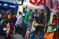 Tränga ihop att se gatakonstnären på den Piccadilly cirkusen Royaltyfri Foto