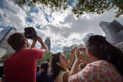 Tränga ihop att se upp på förmörkelse 2017 i New York City Arkivbild