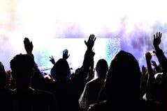 Tränga ihop bifallet och händer som lyfts på en levande konsert royaltyfri foto