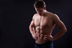 Tränga sig in den sexiga nakna unga mannen som poserar i jeans Royaltyfri Bild