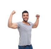 Tränga sig in den starka bicepens för tillfällig man lyckligt leende Fotografering för Bildbyråer