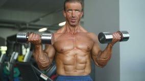 Tränga sig in idrotts- män för den brutala starka kroppsbyggaren som pumpar upp, med hantlar arkivfilmer