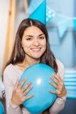 Trängande ballong för lycklig kvinna till hennes bröstkorg och le Royaltyfria Bilder