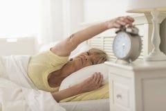 Trängande knapp för kvinna av ringklockan, medan ligga i säng Arkivbild