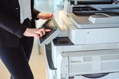 Trängande knapp för kvinna på en kopieringsmaskin i kontoret Royaltyfri Fotografi