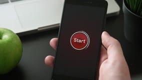 Trängande startknapp på smartphonen arkivfilmer